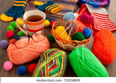 Knitting and comfort. Balls of yarn, knitting needles, basket, tea, glasses provide comfort during knitting. Yarn and knitting needles for making knitted clothes.