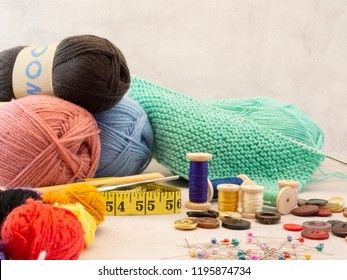Knitting, crochet, sewing equipment on a table. Skeins of wool, little balls of wool, Knitting needles, crochet hooks, tape measure, straight pins and sewing buttons. Copy space on a light background.