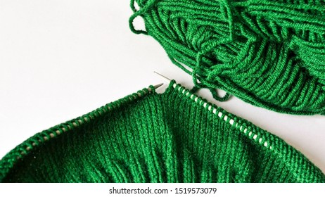 Knitting, elastic, front surface, front loops, green yarn on knitting needles, warm cozy autumn photo