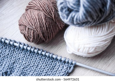 Knitting with grey, white and brown skein as hobby in process
