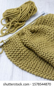 Knitting jumper with merino wool yarn and with a knit stitch.  On a grey wood surface