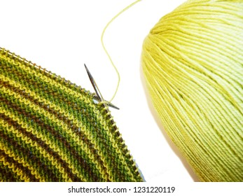 Knitting. Knitted fabric, knitting needles and a skein of yarn. Work process. Hobbies crafts
