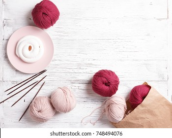 Knitting mood. Paper bag with yarn on a white wooden background. Pink plate with a white cake. Spilled coils of yarn. Pink and dark red coil of yarn
