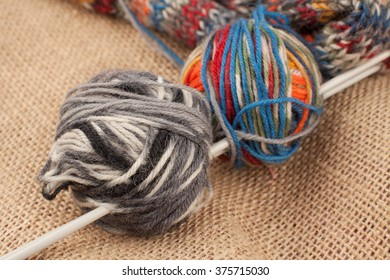 Knitting. Knitting needles, balls of wool and a fragment of the knitted items on a canvas background