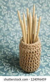 Knitting Needles in Container on Blue Background with Butterflies