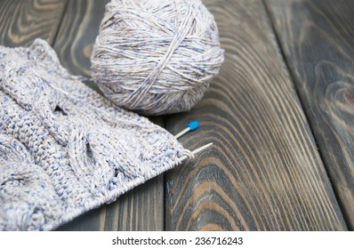 knitting and needles on rustic wooden background