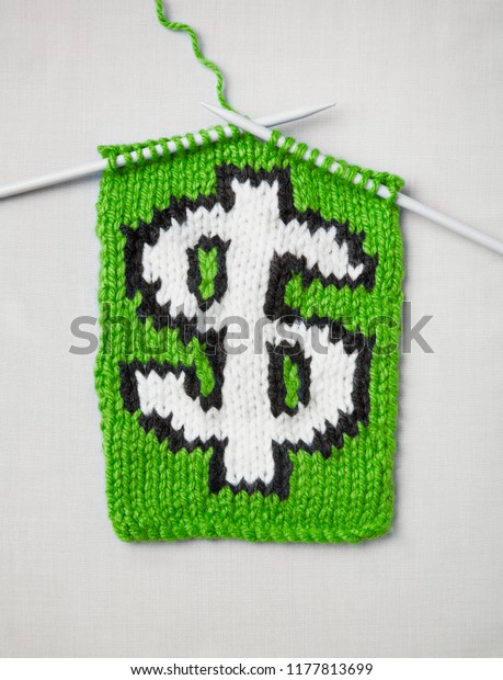Knitting needles and scarf, dollar sign design