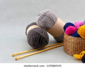 Knitting needles, skeins of wool and a basket filled with colorful balls of wool. Copy space on a light background.