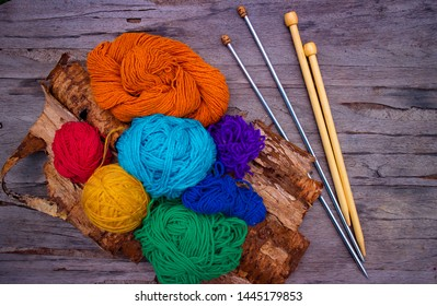 Knitting needles and threads of different colors on a wooden table