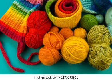 Knitting a rainbow scarf and hat. Basket with balls of wool, knitting needles. Blue background. Favorite work is a hobby.