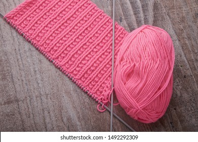 knitting sweaters, or a scarf with a red pattern, thin knitting needles on a white wooden background. Close-up. Copy space.