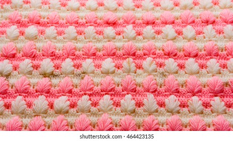 Knitting texture pattern with colors pink and white, flower shape