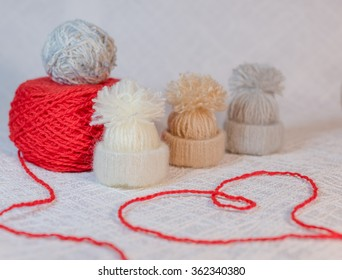 Knitting. Tiny knitted hats on white background