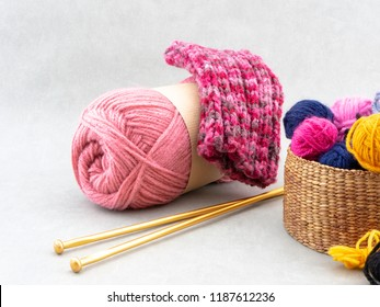 Knitting wool in a basket, a skein of pink wool and gold colored knitting needles. Frontview image with copy space on a white background.