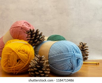 Knitting wool, gold colored knitting needles and pine cones on a fall or winter knitting image. Front view with copy space on a light background.