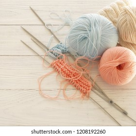 Knitting wool and knitting needles in pastel blue and living coral colors on white wooden background. top view.copy space