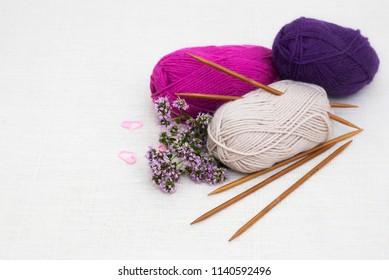 Knitting wool yarn and knitting needles on white linen background