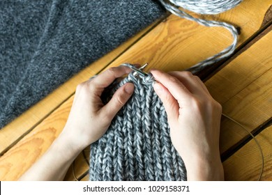 Knitting work: womans hands, swatch and needles close up, wooden background