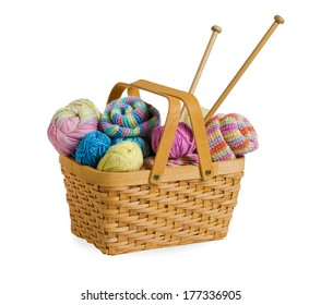 Knitting yarn balls and needles in basket on a white background