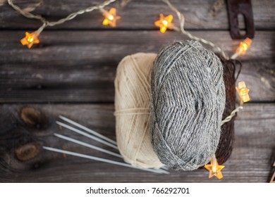 Knitting yarn and needles on wooden background/natural wool knitting background