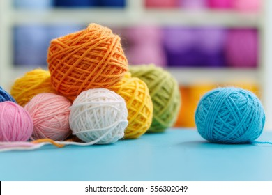 Knitting yarn on blue table against blurred background. Close up of multi colored woolen balls.