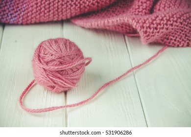 Knitting yarn rolled into ball on a white wooden background.
