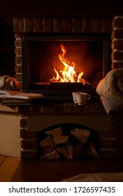 Knitwear and books near fireplace with burning wood indoors. Winter vacation