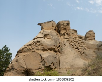 Knobby rock formation with pits and capstones in Medicine Rock State Park in Montana. Thin clouds are above.