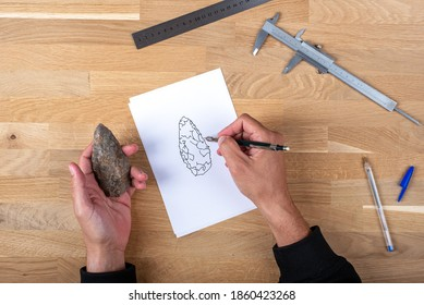 Knolling. Man taking measurements of a paleolithic dagger with a caliper. The man is writing down the measurements in a notepad