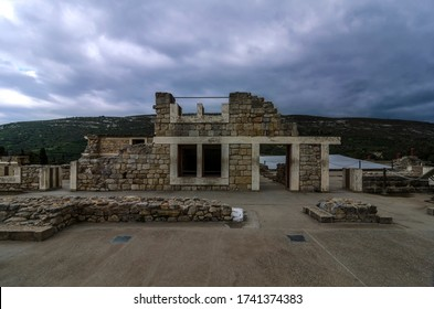 Knossos Palace, Crete / Greece - March 14, 2019: View of the ancient ruins at the archaeological site of Knossos in Heraklion city. Sunset time, cloudy sky
