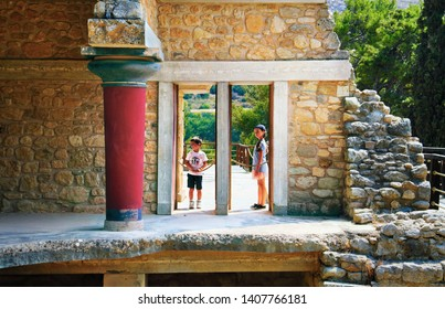 KNOSSOS/GREECE - MAY 8: Two unidenified children look through the reconstructed ancient door on May 08, 2019 in Knossos Palace, Heraklion, Greece, Europe. This is the most visited place on Crete