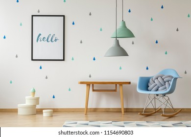 Knot pillow in a baby blue, modern rocking armchair, wooden table and a poster on a wallpaper with colorful droplets in a natural nursery room interior