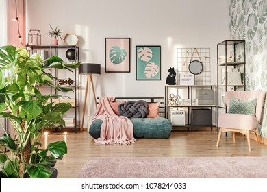 Knot pillow on a designer, emerald green mattress sofa in a living room interior with industrial furniture, a retro powder pink chair and plants