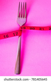 knotted fork with tape measure on pink background, concept of diet and slimming