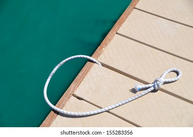 Knotted rope on boat dock ready to tie up a boat