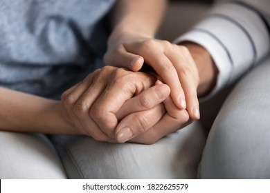 I know you can. Close up of millennial woman grown daughter, grandchild or younger friend holding tight hand of old mother, grandmother, elder relative or colleague helping to overpass life problems