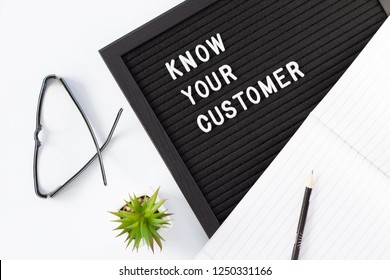 Know Your Customer - business concept, flat lay with white text message on black board, pen and glasses