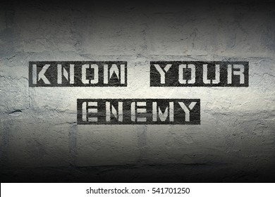 know your enemy stencil print on the grunge white brick wall