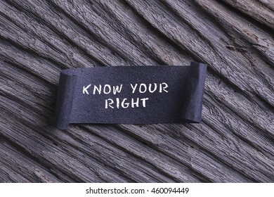 KNOW YOUR RIGHT word written on Black papper with wooden background. RUSTIC AND GRANY EFFECT.