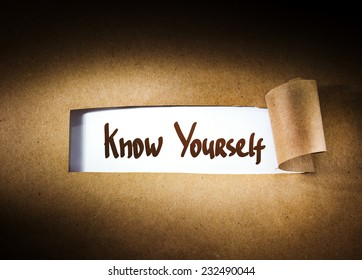 Know yourself  appearing behind torn brown paper