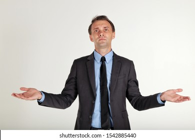 I'don't know.Businessman in a black suit standing and shrugging shoulders,spreading hands  isolated on white background.Spread his arms to pose as a doubt