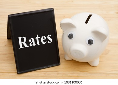 Knowing about the interest rates, A piggy bank with retro freestanding chalkboard on a wood desk with text Rates
