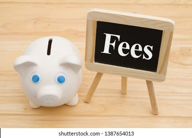 Knowing your bank fees, A piggy bank on a desk with chalkboard with text Fees