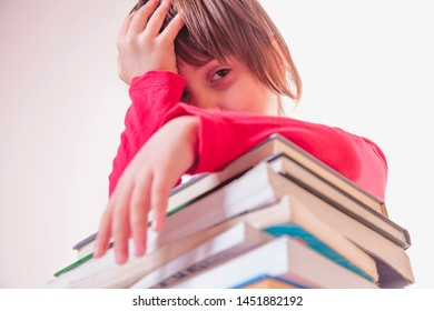 Іnvesting in knowledge is the best investment. Little child girl sitting with lot of books and holding hands to head as symbol of difficult path to success and victory in the future.