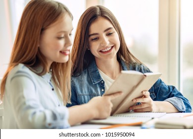 Knowledge is power. Charming teenage girls sitting at the table in the living room and reading a book together while doing their home assignment