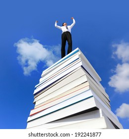 Knowledge is power, Excited business man arise arm cheering and celebrating on a stack Of Books