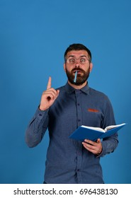 Knowledge and scheduling concept. Notebook in blue color in guys hands isolated on blue background. Professor has new idea. Teacher wears glasses and holds organizer. Man with beard, book and marker