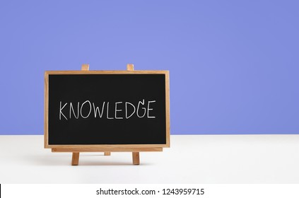 knowledge word on blackboard and violet background
