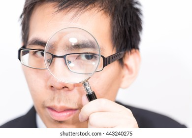 I known keyword of your business, Business asian man Looking At camera Through Magnifying Glass close up on white