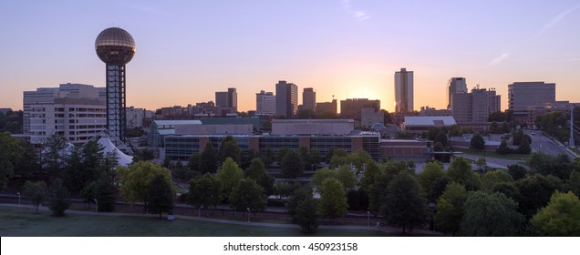 Knoxville city skyline is backlit by the orange hues of sunrise